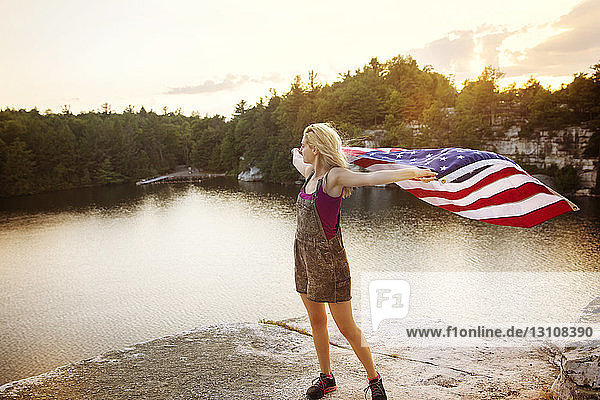 Young woman holding American flag while standing on rock by lake