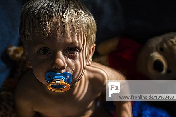 Porträt eines Jungen ohne Hemd mit Schnuller im Mund zu Hause