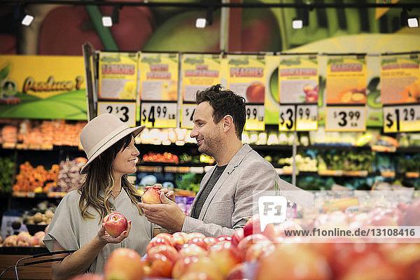 Lächelndes Paar beim Apfeleinkauf im Supermarkt