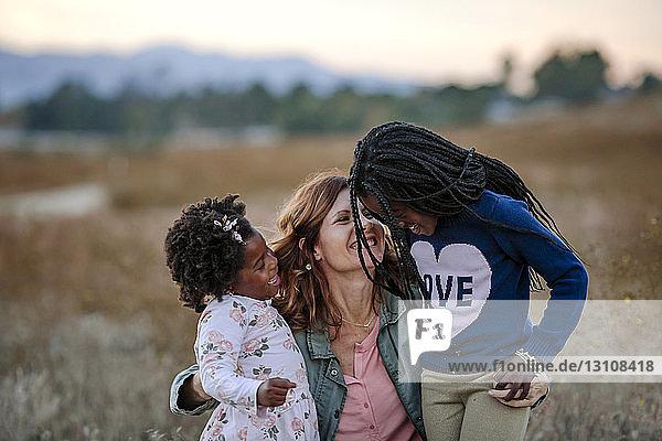 Lächelnde Mutter spielt mit Töchtern im Wald bei Sonnenuntergang