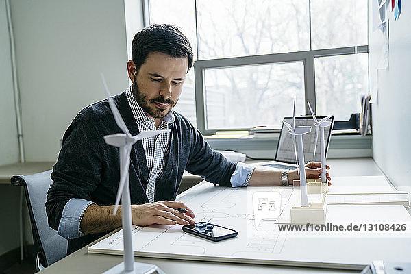 Geschäftsmann benutzt Smartphone  während er Modelle von Windkraftanlagen auf dem Schreibtisch arrangiert
