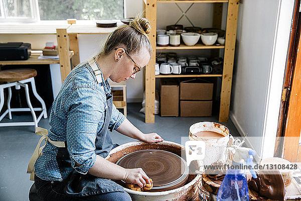 Seitenansicht der Frau  die in der Werkstatt die Töpferscheibe reinigt