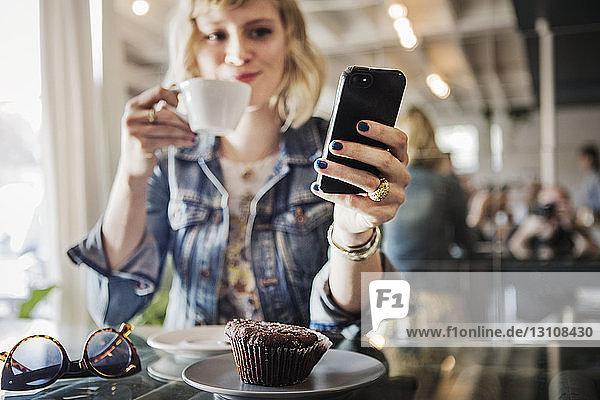 Frau hält Smartphone in der Hand  während sie im Cafe steht