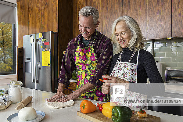 Lächelnde Frau schneidet Paprika  während der Mann zu Hause in der Küche Pizzateig macht