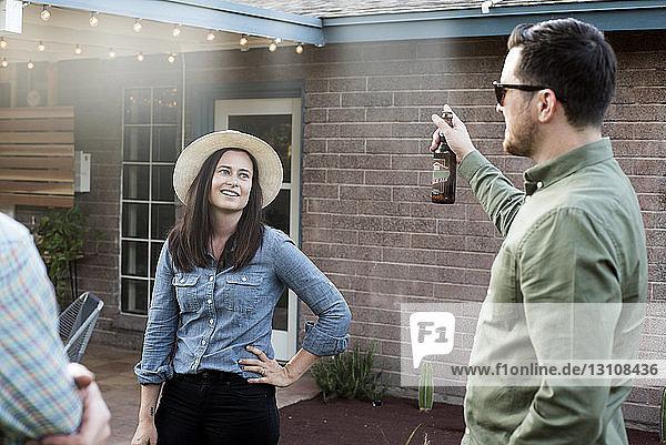 Paar redet  während es mit einem Freund im Hinterhof steht