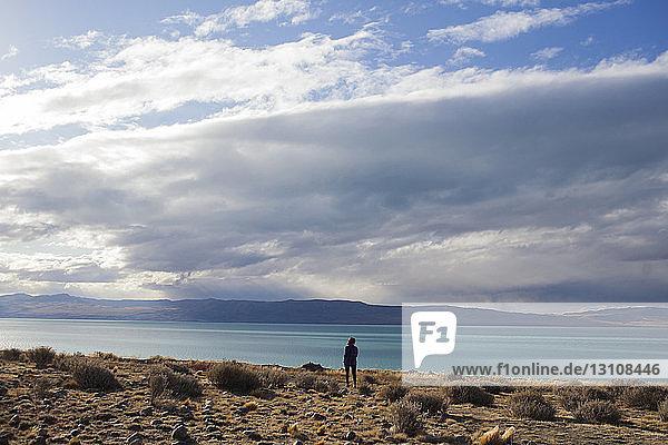 Rückansicht einer am Seeufer stehenden Frau vor bewölktem Himmel