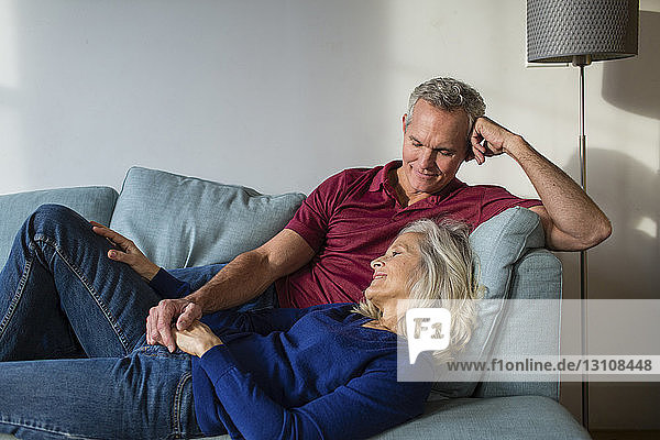Loving couple relaxing while lying on sofa at home