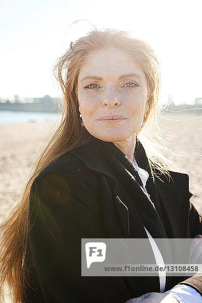 Porträt einer selbstbewussten reifen Frau am Strand während eines sonnigen Tages