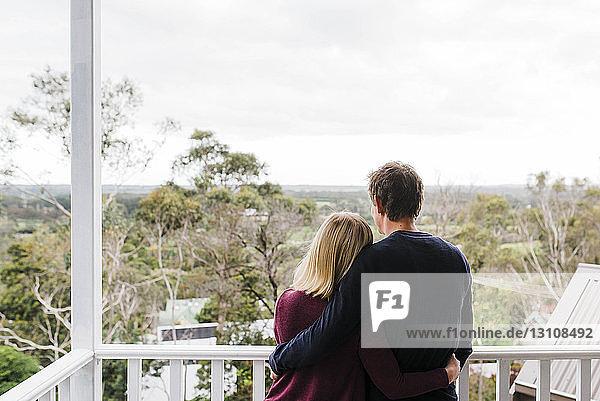 Rückansicht eines auf dem Balkon stehenden Paares mit Armen um die Taille