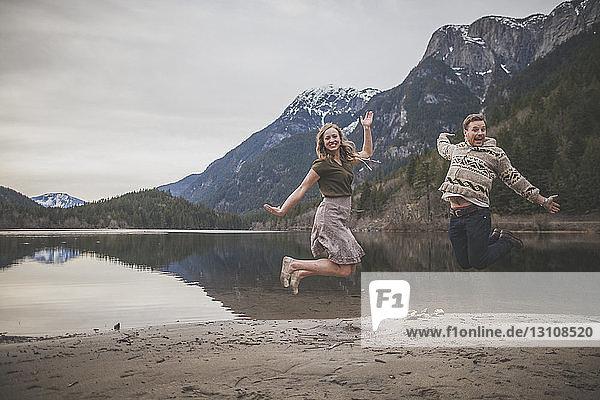 Ganzfiguriges Porträt eines verspielten jungen Paares  das am Seeufer im Silver Lake Provincial Park springt