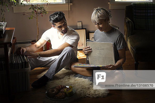 Junges Paar wählt Vinyl-Schallplatten  während es zu Hause auf dem Boden sitzt
