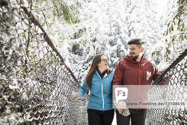 Smiling couple walking on footbridge amidst forest at Lynn Canyon Park during winter