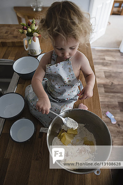 High angle view of girl mixing batter in bowl while sitting on kitchen counter