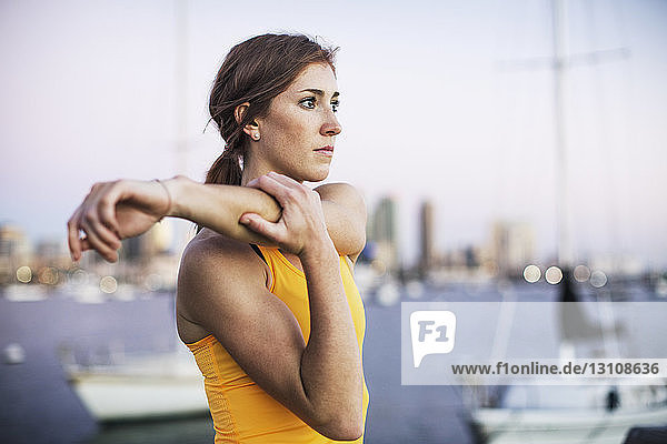 Determined female athlete stretching arm by harbor against clear sky