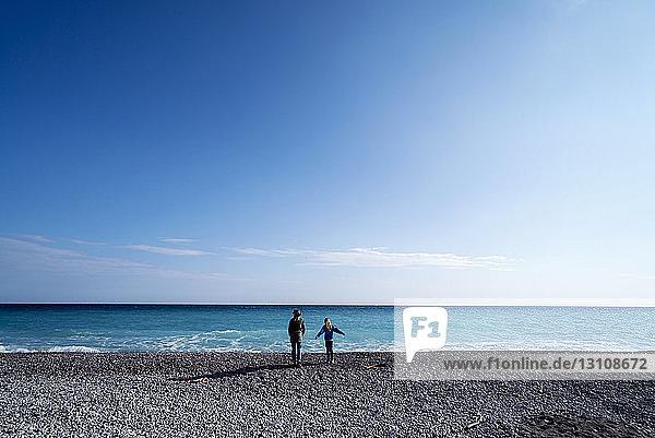 Rückansicht einer älteren Frau  die mit einem Mädchen am Strand gegen den Himmel steht