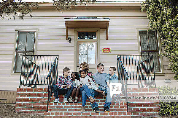 Glückliche Familie in voller Länge beim Sitzen auf den Stufen am Eingang des Gebäudes