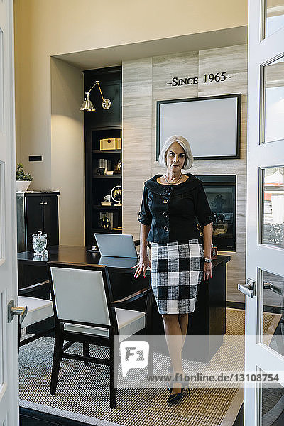 Porträt einer selbstbewussten Geschäftsfrau im Amt in voller Länge durch die Tür gesehen