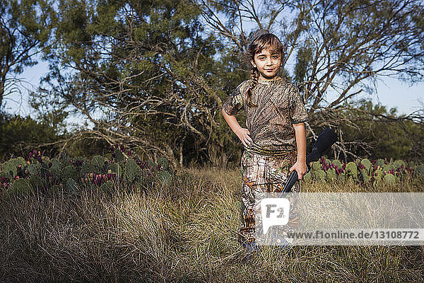 Portrait of girl with rifle on grassy field