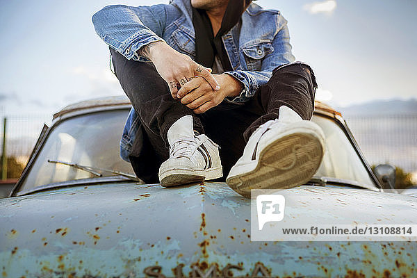 Low section of fashionable man sitting on abandoned car hood
