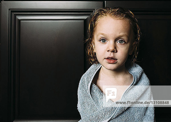 Portrait of boy wrapped in towel at home