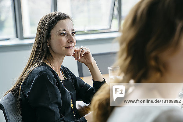 Businesswoman looking away while sitting by colleague in office