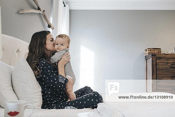 Seitenansicht einer Mutter  die ihren Sohn küsst  der zu Hause auf dem Bett sitzt