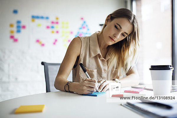Serious businesswoman writing on adhesive notes at table in office