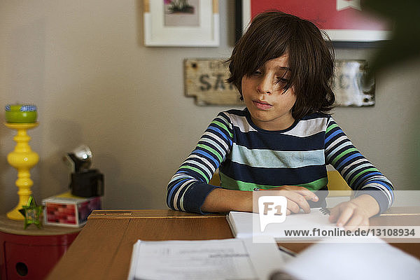 Boy studying at table in home