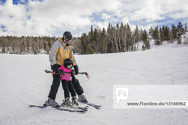 Father with daughter skiing on snow covered landscape against cloudy sky at forest