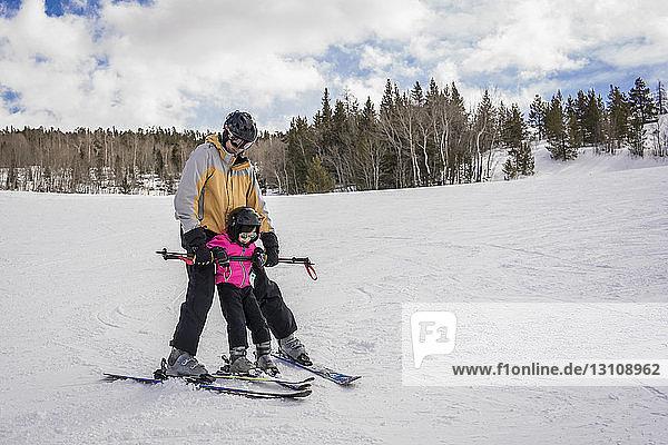 Vater mit Tochter beim Skifahren in schneebedeckter Landschaft vor bewölktem Himmel im Wald