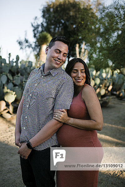 Happy couple standing against plants in park during sunset