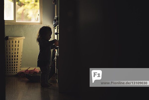 Side view of silhouette baby girl standing by cabinet at home