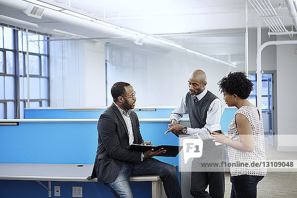 Colleagues discussing in empty office