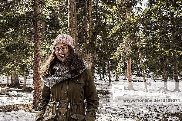 Cheerful woman wearing warm clothing while standing at forest during winter
