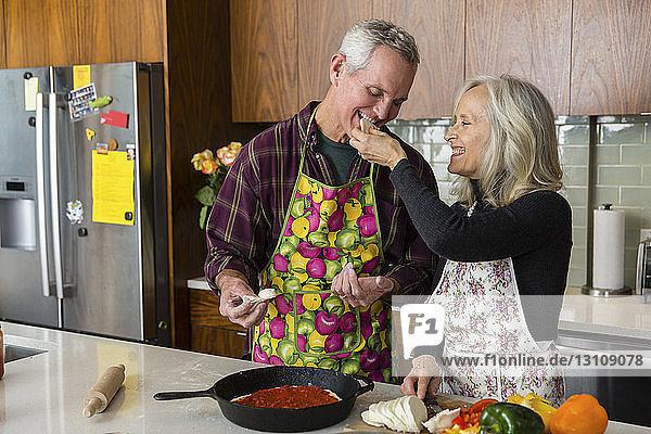 Fröhliche Frau  die einen Mann mit Käse füttert  während sie zu Hause in der Küche das Essen zubereitet