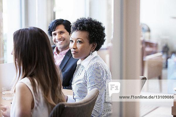 Mittlere erwachsene Frau  die ihren Kollegen während der Besprechung im Büro ansieht