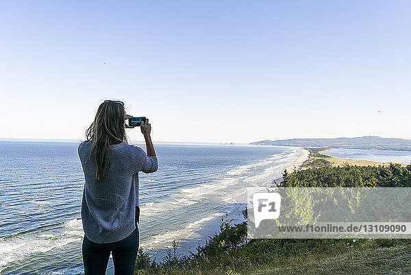 Rear view of woman photographing sea while standing against clear sky