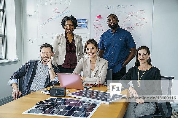 Porträt von lächelnden Geschäftsleuten durch Solarpanel-Modelle auf dem Schreibtisch