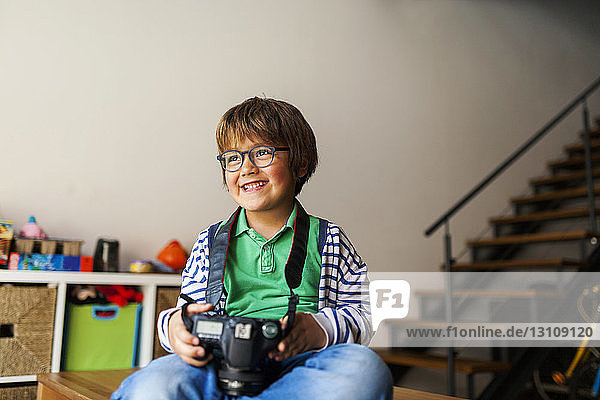 Boy with camera looking away while sitting on table at home