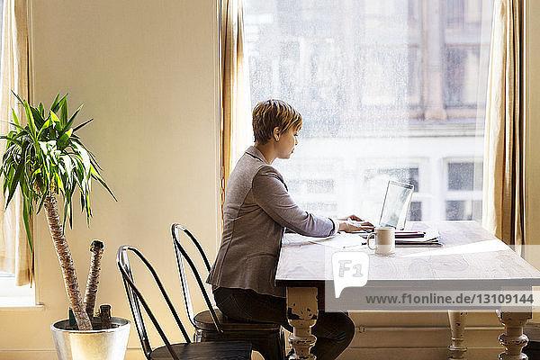 Mittlere erwachsene Geschäftsfrau mit Laptop am Schreibtisch im Büro