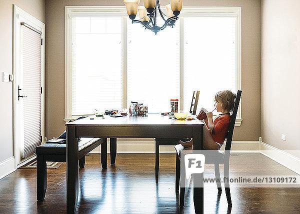 Boy enjoying drink while sitting at table