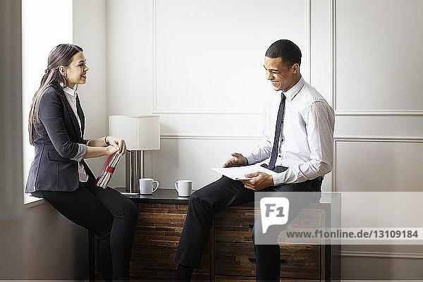 Glückliche Kollegen sitzen im Büro