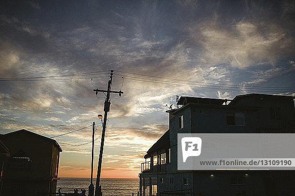 Niedrigwinkelansicht von Silhouettengebäuden am Strand vor bewölktem Himmel bei Sonnenuntergang