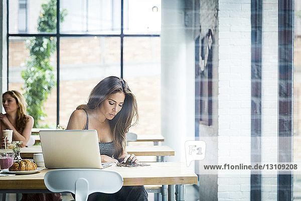 Frau  die ein Smartphone benutzt  während sie in einem Café mit einem Freund im Hintergrund durch ein Fenster gesehen wird