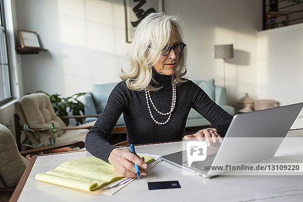 Seriöse ältere Frau benutzt Laptop-Computer beim Bezahlen von Rechnungen zu Hause