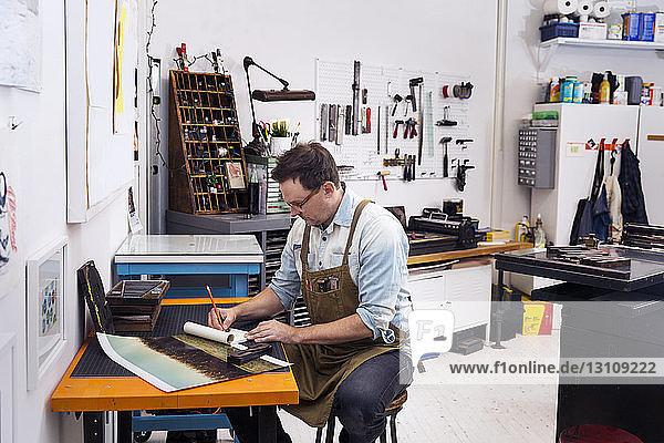 Ernsthafter Mann schreibt auf Papier  während er in einer Druckerpresse sitzt
