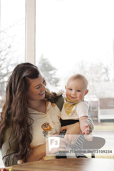 Glückliche Mutter  die zu Hause sitzt und ihr Kind austrägt