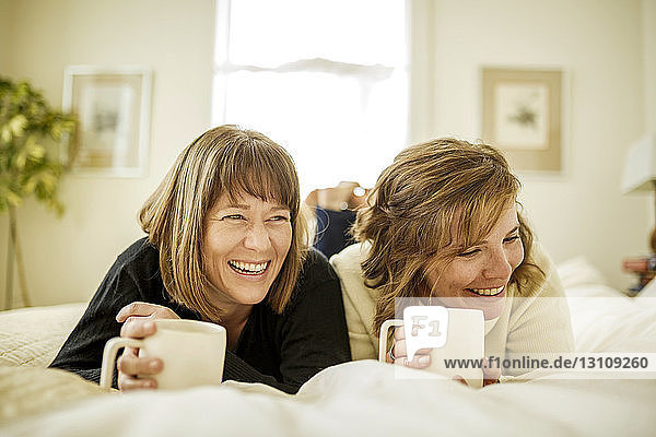 Happy sisters lying on bed at home