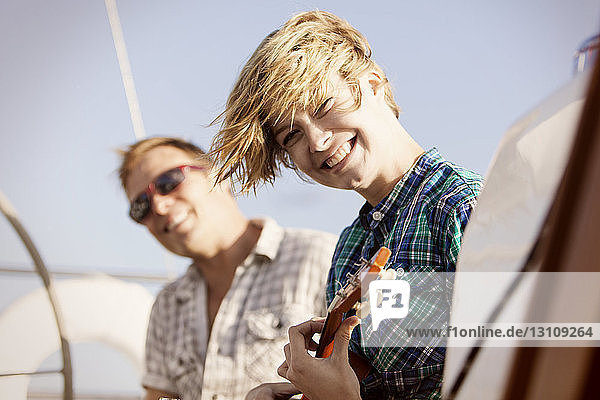 Happy woman holding guitar while travelling with friend on boat