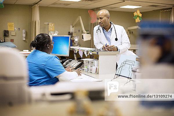 Arzt im Gespräch mit Krankenschwester im Krankenhaus